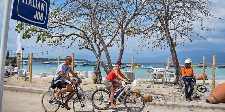 Dua orang wisatawan asing mengendarai sepeda di kawasan wisata Gili Trawangan, Desa Gili Indah, Kecamatan Pemenang, Tanjung, Lombok Utara, NTB, Rabu (8/8/2018). Pascagempa yang melanda daerah Lombok Utara, sebagian wisatawan asing memilih tetap tinggal di kawasan wisata Gili Trawangan.