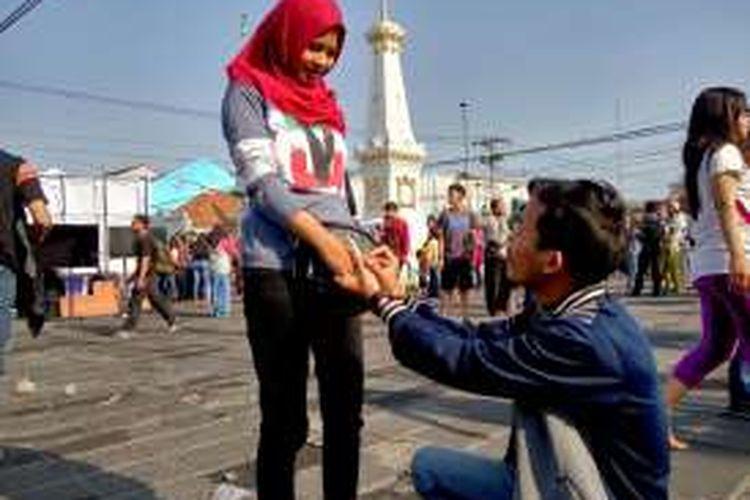 Nanang Kristanto (28) saat melamar kekasihnya Dian Paramita (24) saat momen gerhana matahari di Tugu Yogyakarta, Rabu (9/3/2016) pagi.