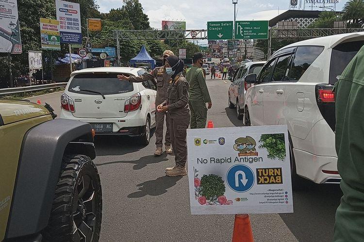 Sejumlah petugas sedang memeriksa surat rapid antigen sebagai syarat untuk ke Puncak Bogor di Simpang Gadog, Kabupaten Bogor, Jawa Barat, Jumat (12/2/2021)