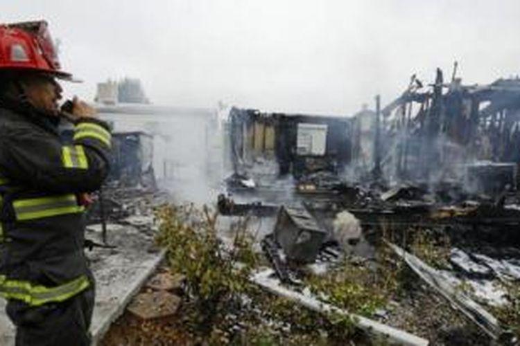 Seorang petugas pemadam kebakaran mengamati rumah-rumah yang hancur akibat gempa di Napa, California, AS (24/8/2014).