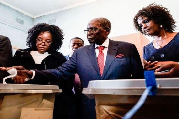 Mantan presiden Zimbabwe Robert Mugabe (tengah) memasukkan surat suara dengan didampingi istrinya Grace dan putrinya Bona.