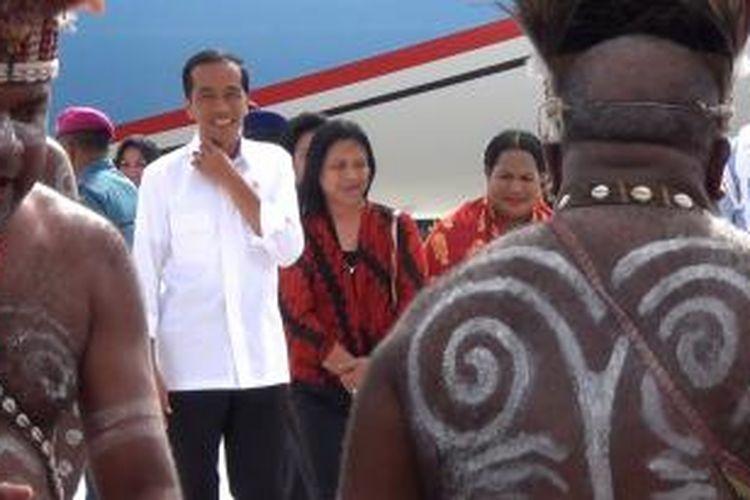 Presiden Joko Widodo bersama istri saat disambut dengan tarian adat di Bandara Sentani, Jayapura, Sabtu (27/12/2014).