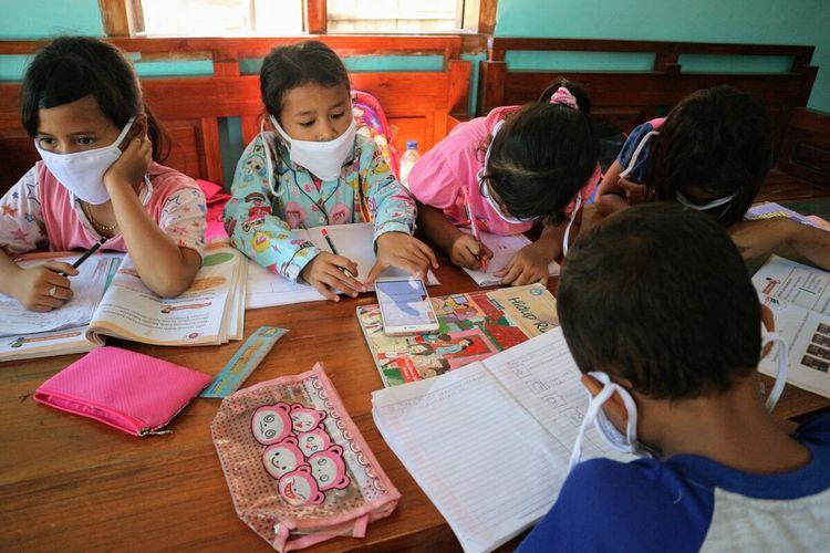 Sejumlah siswa Sekolah Dasar Negeri (SDN) di Desa Marmoyo, Kecamatan Kabuh, Kabupaten Jombang, Jawa Timur, mengerjakan tugas dengan berkelompok menggunakan handphone secara bergantian di rumah warga, Rabu (22/7/2020).