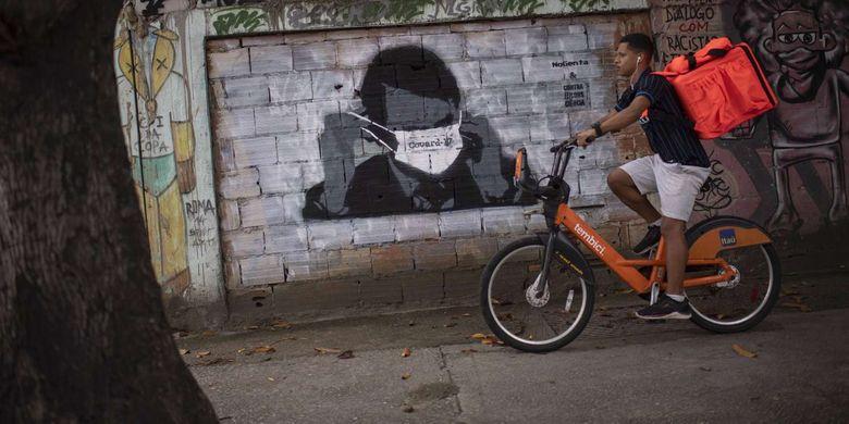 Seorang warga bersepeda melintas di depan gambar mural Presiden Brazil Jair Bolsonaro di Rio de Janeiro, Brazil, 24 Maret 2020. Pandemi Covid-19 yang disebabkan oleh virus corona menjadi insipirasi seniman grafiti untuk memberikan peringatan dan motivasi bagi warga dalam menghadapi virus tersebut.