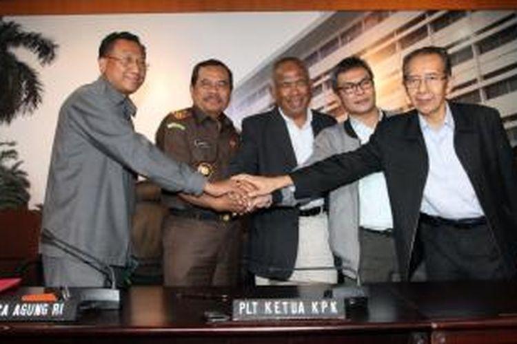 Plt Ketua KPK Taufiqurahman Ruki (tengah) bersama Jaksa Agung AM Prasetyo (dua kiri), Jampidus Widyo Pramono (kiri), Plt Komisioner KPK Johan Budi (dua kanan), dan Komisioner KPK Zulkarnain saling berjabat tangan usai menggelar konferensi pers bersama di Gedung Kejaksaan Agung, Jakarta, Senin (23/2/2015). Dalam kesempatan tersebut KPK dan Kejagung menyatakan kesiapannya untuk bersinergi dalam memberantas korupsi.