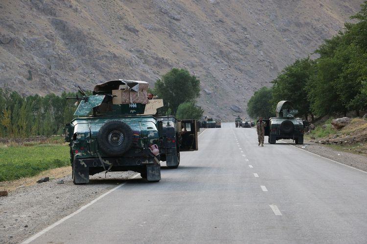 Konvoi tentara Afghanistan berhenti sejenak di garis depan pertempuran melawan Taliban, dekat kota Badakhshan, Afghanistan utara, Minggu (4/7/2021). Lebih dari 1.000 personel melarikan diri ke negara tetangga, Tajikistan, karena kalah bentrok melawan Taliban.