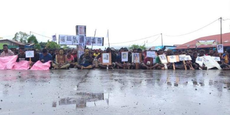 Masing-masing massa memegang foto para korban konflik