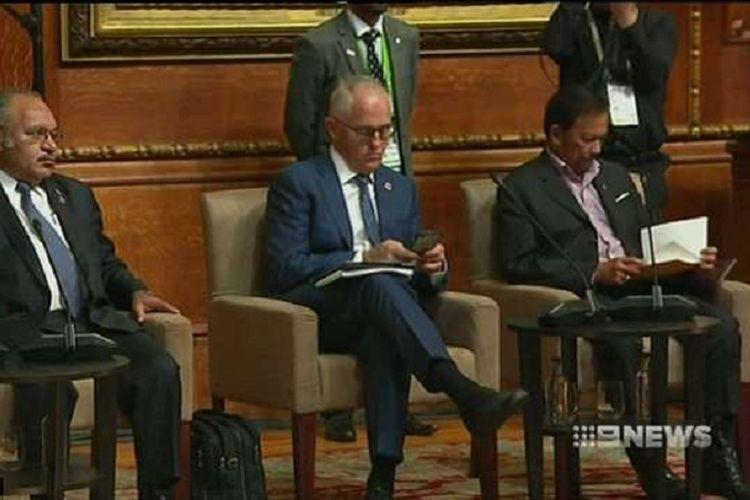 PM Malcolm Turnbull tertangkap kamera sedang sibuk memainkan ponselnya di saat PM Theresa May sedang berpidato di hadapan para pemimpin negara-negara Persemakmuran di London.