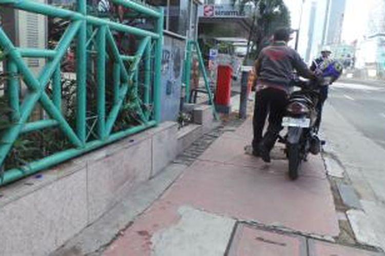 Pria ini terlihat mendorong motor di trotoar Jalan MH Thamrin, Jakarta Pusat, Rabu (17/12/2014). D jalur itu, sepeda motor dilarang melintas.