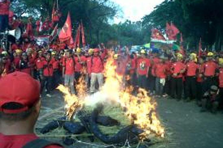 Buruh bakar gurita di depan istana  Setelah aksi demo, Buruh membakar replika gurita yang melambangkan sistem pemerintahan yang rakus, di Depan Istana Merdeka,Jakarta, Senin (16/09/2013).