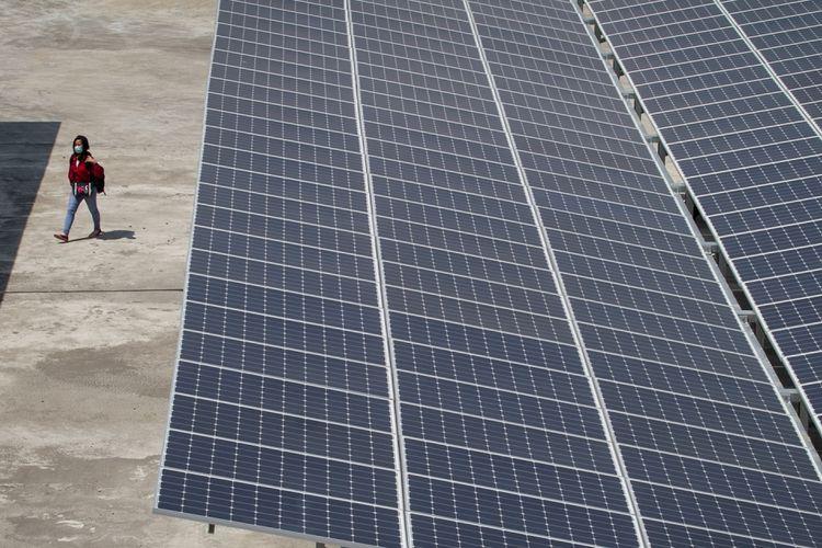 Warga melintas di bawah instalasi panel surya di Terminal Tirtonadi, Solo, Jawa Tengah, Rabu (26/7/2017). Proyek Kementerian Perhubungan tersebut mampu menghasilkan tenaga listrik 500 kilo volt ampere (kVA) atau 500.000 watt sebagai upaya penghematan energi listrik operasional Terminal tipe A Tirtonadi.