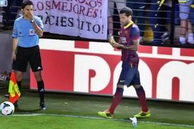 Bek Barcelona, Dani Alves, memakan pisang yang dilempar suporter Villarreal dalam pertandingan Primera Division, Minggu (27/4/2014).