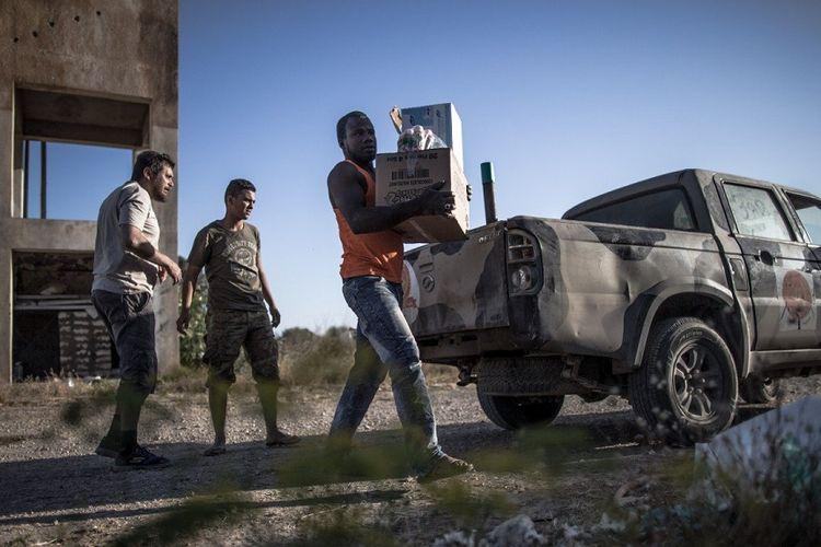 Personel dari pasukan pemerintah yang didukung PBB mendistribusikan makanan dan obat-obatan ke warga yang terjebak konflik di dekat al-Sawani di Tripoli.