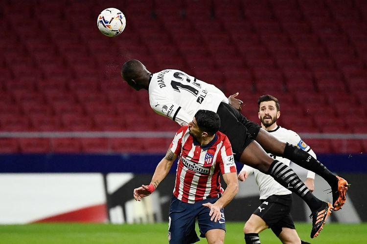 Bek Valencia asal Perancis, Mouctar Diakhaby, menyundul bola dalam pertandingan Liga Spanyol antara  Atletico Madrid vs Valencia CF di Stadion Wanda Metropolitano di Madrid pada 24 Januari 2021.
