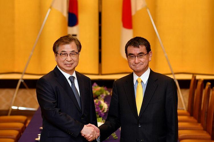 Menteri Luar Negeri Jepang Taro Kono (kanan) berjabat tangan dengan Kepala Badan Intelijen Korea Selatan Suh Hoon usai pertemuan di Tokyo, Senin (12/3/2018).