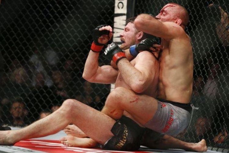 Georges St-Pierre (kanan) mencekik Michael Bisping (kiri) dalam ajang UFC 127, sabtu (04/11/20170.