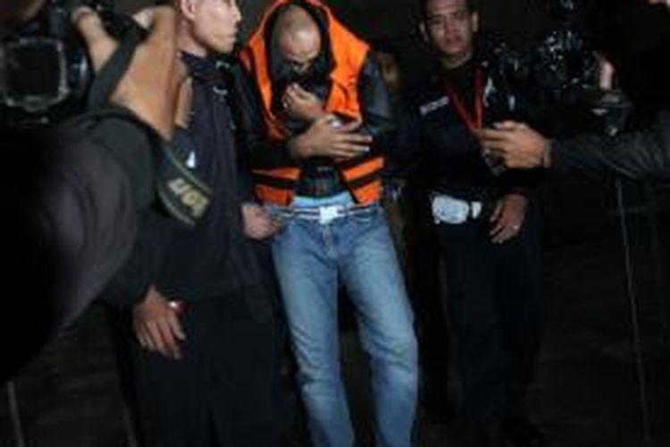 Deviardi atau Ardi berusaha menutupi wajahnya dengan jaket saat hendak ditahan usai diperiksa selama lebih dari 22 jam oleh Komisi Pemberantasan Korupsi (KPK) di Gedung KPK, Jalan HR Rasuna Said, Kuningan, Jakarta Selatan, Rabu (14/8/2013). Pelatih golf ini diduga menjadi kurir dalam kasus penyuapan Kepala SKK Migas, Rudi Rubiandini dan ditangkap KPK pada Selasa (13/8/2013) malam.