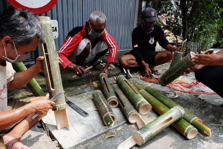 Warga bergotong-royong membuat alat komunikasi tradisional kentongan dari bambu di Kadipiro, Solo, Selasa (21/4/2020). Wali Kota Solo, FX. Hadi Rudyatmo mengintruksikan warga membuat kentongan dan mengaktifkan kembali Sistem Keamanan Lingkungan (Siskamling), guna mengantisipasi potensi kriminalitas yang meningkat di tengah pandemi COVID-19 ini. ANTARA FOTO/Maulana Surya/foc.