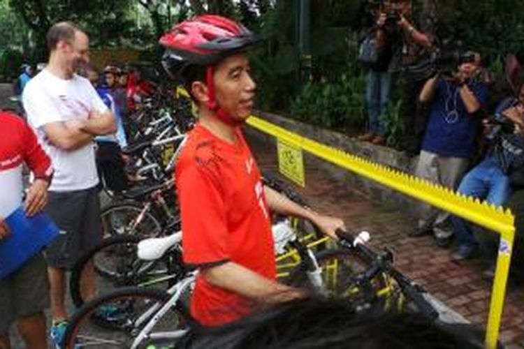Gubernur DKI Jakarta Joko Widodo mengenakan konstum Persija dan bersepeda menuju Balaikota, Jumat (3/1/2014).