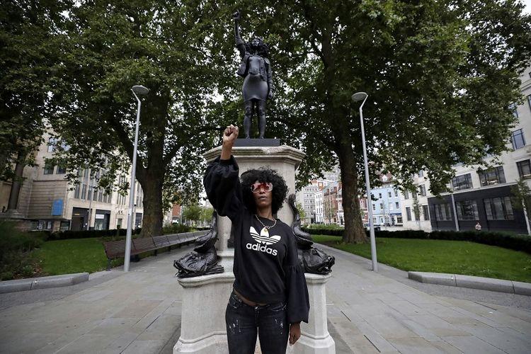 Jen Reid berpose untuk foto di depan resin hitam baru dan patung baja yang menggambarkan dirinya, berjudul Kebangkitan Kekuatan (Jen Reid) 2020 oleh seniman Marc Quinn setelah patung itu diletakkan pagi hari waktu setempat Rabu (15/7/2020) di atas monumen dari patung yang sebelumnya ditumbangkan, patung Edward Colston.