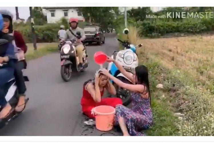Tangkapan layar dari video aksi mandi keramas di tepi jalan raya Meri Kota Mojokerto yang dilakukan 2 wanita di Mojokerto, Jawa Timur.