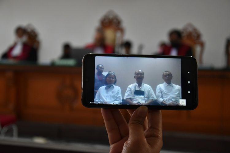 Tampak layar ponsel dan televisi di Pengadilan Negeri (PN) Bandung, Jalan L.L.R.E Martadinata, Kota Bandung, tengah memperlihatkan tiga petinggi Sunda Empire yang berada di Tahanan Polda Jabar. Sidang perdana dengan agenda pembacaan dakwaa tiga terdakwa ini dilakukan secara virtual, Kamis (18/6/2020).