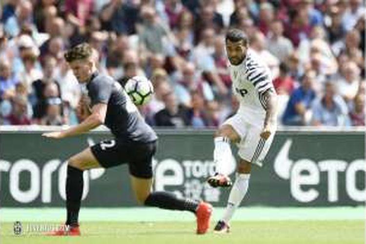 Bek sayap Juventus, Daniel Alves (kanan), melepaskan umpan silang saat melawan West Ham United pada partai uji coba di di London Stadium, Sabtu (7/8/2016).