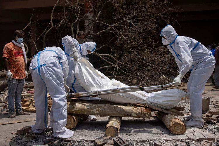 Kerabat menyiapkan jenazah seseorang, yang meninggal karena penyakit virus corona (COVID-19), untuk dikremasi di tempat krematorium di New Delhi, India, Rabu (28/4/2021).