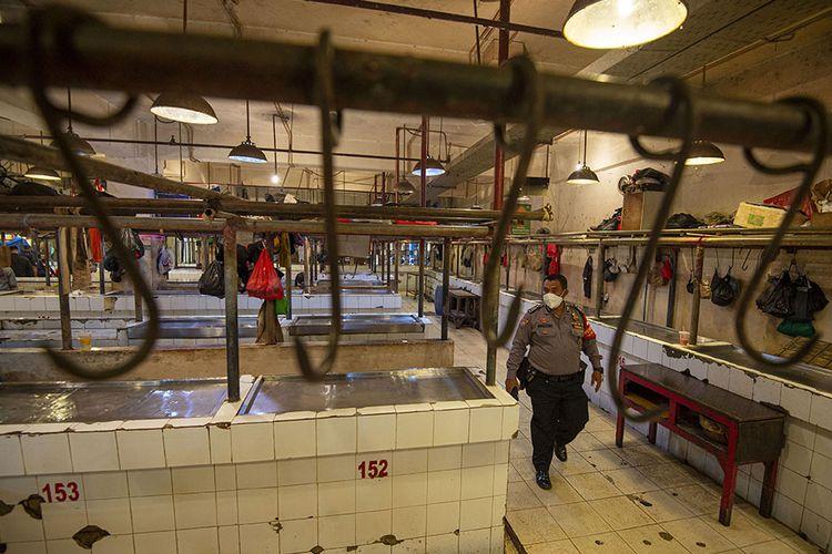 Polisi berjalan di los daging yang sepi akibat aksi mogok pedagang di Pasar Senen, Jakarta, Rabu (20/1/2021). Para pedagang daging sapi di sejumlah pasar di kawasan Jakarta, Bogor, Depok, Tangerang, dan Bekasi (Jabodetabek) menggelar aksi mogok jualan mulai Rabu hingga Jumat (22/1) sebagai bentuk protes kepada pemerintah atas tingginya harga daging sapi yang sudah berlangsung sejak akhir 2020. Saat ini harga daging sapi mencapai sekitar Rp130 ribu per kilogram.