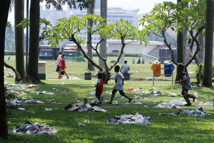 Pengunjung melntas di antara sampah yang masih berserakan di kawasan Monumen Nasional, Jakarta, Minggu (29/4/2018). Sampah yang berserakan merupakan sisa dari acara pembagian sembako yang berlangsung pada Sabtu (28/4/2018) di lokasi tersebut.