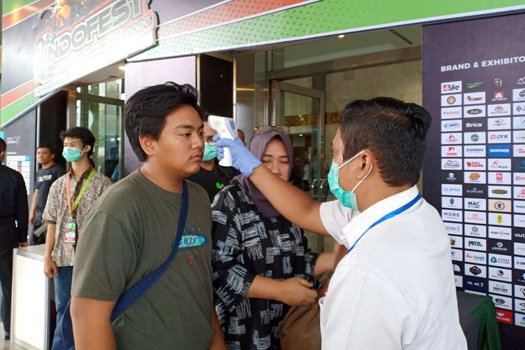 Petugas memeriksa suhu tubuh pengunjung di pintu masuk Indofest 2020