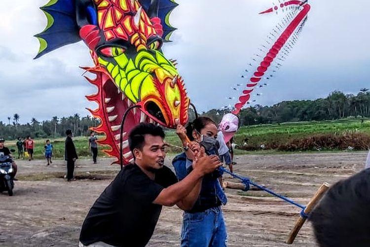 Wisata alternatif di Bantul - Seorang wisatawan sedang menaiki layangan naga raksasa di Kabupaten Bantul, Yogyakarta.