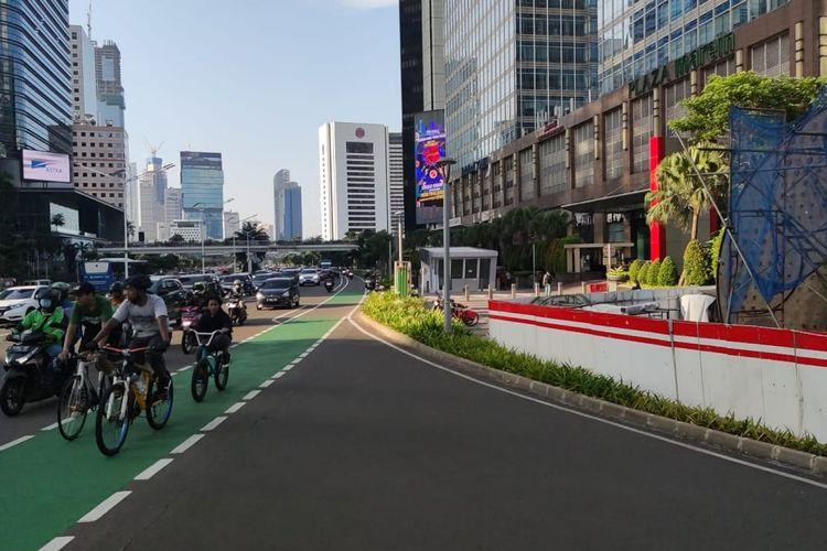 Pesepeda melintasi proyek Tugu Sepeda di Jalan Sudirman, Jakarta Pusat, Jumat (9/4/2021).