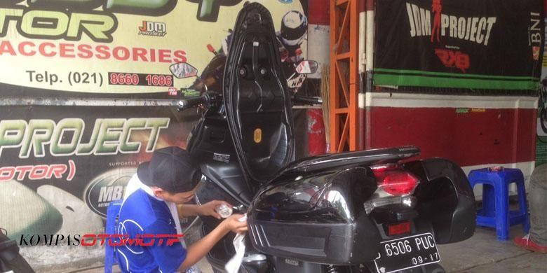 Salah seorang pegawai JDM Project sedang melakukan poles bodi di sepeda motor Honda PCX.