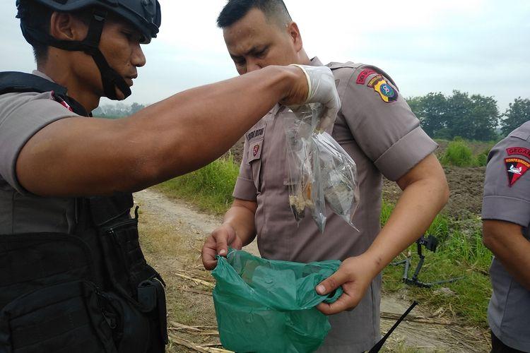 Petugas memasukkan plastik berisi bahan-bahan dari bom kaleng sarden yang ditemukan di tambak milik Habibullah, tersangka kasus bom bunuh diri di Mako Polrestabes Medan pada Rabu pagi (13/11/2019). Dari discrafter terhadap bom kaleng itu, petugas menemukan potongan besi dan baut.