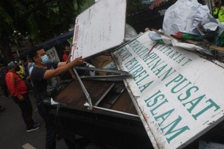 Petugas membongkar atribut-atribut saat melakukan penutupan markas DPP Front Pembela Islam (FPI) di Petamburan, Jakarta, Rabu (30/12/2020).