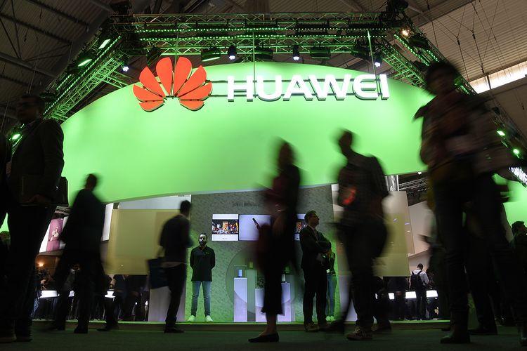 Pengunjung melintas di depan stan perusahaan teknologi asal China, Huawei, pada hari pertama ajang Mobile World Congress di Barcelona, Spanyol, Senin (27/2/2017).