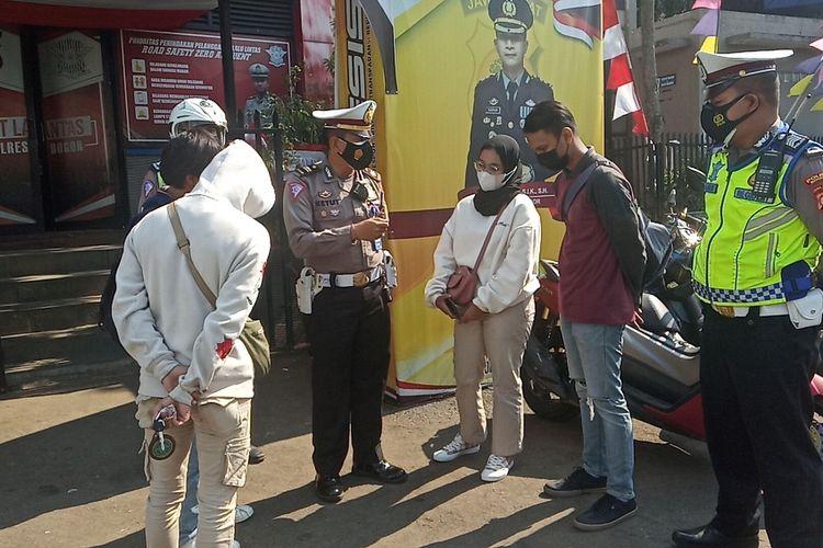 KBO Lantas Polres Bogor Iptu Ketut sedang mengamankan pelaku tukar pelat nomor kendaraan saat ganjil genap di Puncak Bogor, Jawa Barat, Sabtu (4/9/2021).