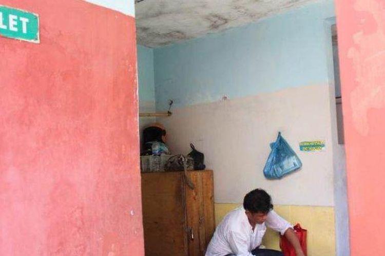 Nurul Mukminin sopir angkot memandikan bayi Bilqis Choirun Nisa yang masih berusia 3,5 bulan di depan toilet Terminal Mangkang Semarang, Jumat (7/2/2020) pagi. (TRIBUN JATENG/IWAN ARIFIANTO)