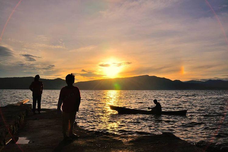 Momen sunset yang dinikmati dari pantai di Samosir