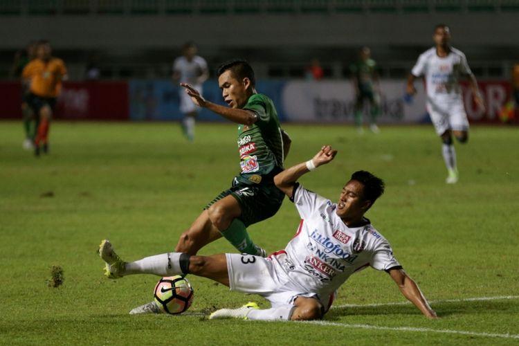 Pemain PS TNI Erwin Ramdani (kiri) berebut bola dengan pemain Bali United I Made Andhika Pradana Wijaya (kanan) pada pertandingan lanjutan Liga 1 di Stadion Pakansari, Cibinong, Bogor, Senin (10/7/2017). Bali United menang setelah menundukkan PS TNI dengan skor akhir 4-3.
