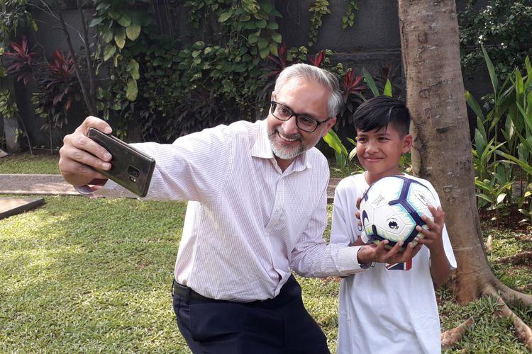 Muhammad Rizky (13), bocah korban Gempa Palu yang diundang ke markas Manchester City, saat bersama dengan Duta Besar Inggris untuk Indonesia, ASEAN dan Timor Leste, Moazzam Malik, di Kedubes Inggris di Jakarta, Kamis (9/5/2019).