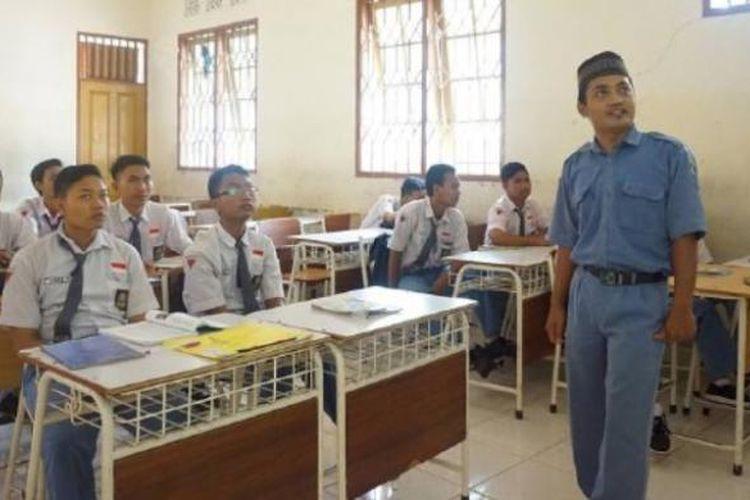 Moch Hamzah Rifwan (33), guru tidak tetap di SMKN 2 Surabaya, Jawa Timur, mengajar mata pelajaran Pendidikan Agama Islam, Selasa (10/1). Mulai tahun ini, gajinya sebagai guru tidak tetap dibayar menggunakan uang sumbangan pembinaan pendidikan setelah Pemerintah Kota Surabaya tidak bisa mencairkan dana bantuan operasional daerah karena pengelolaan SMA/SMK beralih dari pemerintah kabupaten/kota ke pemerintah provinsi.