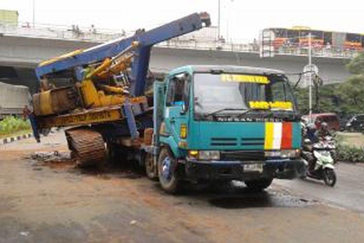 Sebuah alat berat jatuh dari kontainer di Jalan Sunter Bouluevard, Jakarta Utara, Jumat (14/3/2014). Kejadian ini menimbulkan kemacetan panjang.