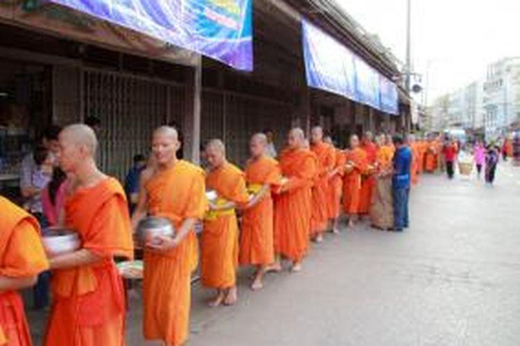 Dalam foto ini sekelompok biarawan Buddha menerima sumbangan makanan dari warga di Muang Phrae, Thailand.