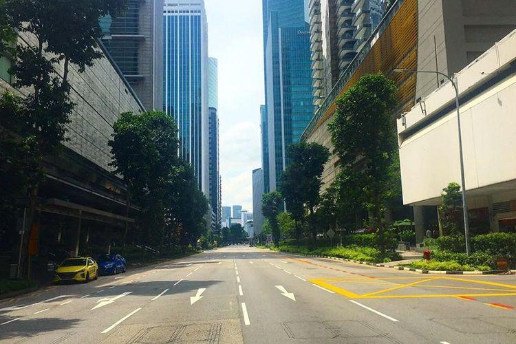 Jalan raya Shenton Way di kawasan distrik bisnis Tanjong Pagar, Singapura terlihat lenggang, Senin siang (18/05/2020). Jalanan Singapura memang terlihat lebih sunyi di mana hanya ada segelintir kendaraan yang melintas sejak lockdown parsial atau circuit breaker diberlakukan pada 7 April lalu. Singapura akan mencabut lockdown parsial pada 1 Juni mendatang