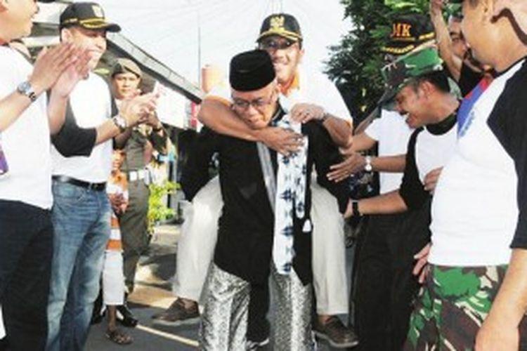 Wali Kota Jakarta Barat H Fatahillah digendong oleh Ketua RW 017 Kelurahan Kemanggisan karena jalan tembus Kompleks Hankam ke Kemanggisan telah terwujud, Minggu (23/6/2013).