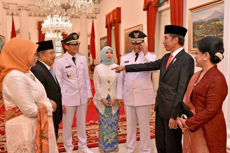 Presiden Joko Widodo (kedua kanan) dan Ibu Negara Iriana Joko Widodo (kanan) berbincang dengan Wapres Jusuf Kalla (kedua kiri), Gubernur DKI Jakarta Anies Baswedan (ketiga kanan), Ibu Fery Farhati Ganis Baswedan (kiri), Wakil Gubernur DKI Jakarta Sandiaga Uno (ketiga kiri) dan Ibu Nur Asia Uno (tengah) seusai acara pelantikan di Istana Negara, Jakarta, Senin (16/10/2017). Anies Baswedan dan Sandiaga Uno resmi menjabat sebagai Gubernur dan Wakil Gubernur DKI Jakarta periode 2017-2022.