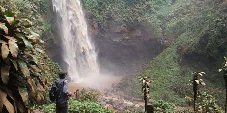 Wisatawan menyaksikan Air Terjun Cipendok, Cilongok Banyumas, Jateng dari kejauhan. Dedaunan pohon dan tumbuhan hijau di sekitar air terjun berubah coklat dan kotor karena terkena percikan air terjun yang keruh bercampur lumpur.