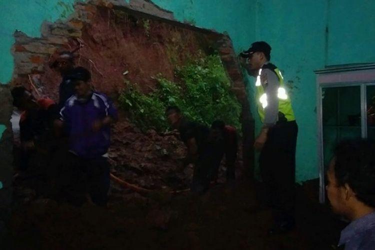 Warga dan anggota Polres Batang menyingkirkan reruntuhan longsor di Desa Candigugur, Batang Jawa Tengah.